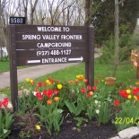 Campground sign with red and yellow flowers