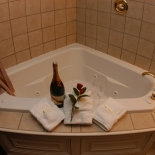 corner bathtub with a bottle of wine